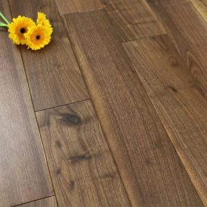 Dark brown Walnut floor with a single yellow flower on top